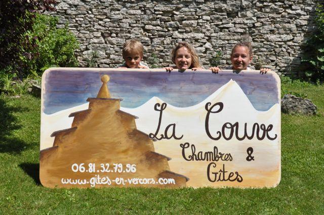 Pauline entourée de Félix et Lucie derrière la nouvelle pancarte